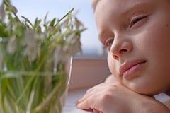 Cierre del muchacho del niño para arriba que mira snowdrops Imagen de archivo