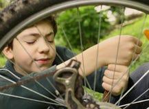 Cierre del neumático de la bicicleta de la reparación del muchacho del adolescente encima de la foto del verano Foto de archivo