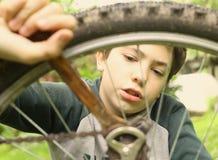 Cierre del neumático de la bicicleta de la reparación del muchacho del adolescente encima de la foto del verano Imagenes de archivo