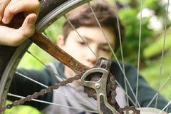 Cierre del neumático de la bicicleta de la reparación del muchacho del adolescente encima de la foto del verano Fotografía de archivo libre de regalías