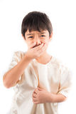 Cierre del niño pequeño su nariz con la cara infeliz imagen de archivo