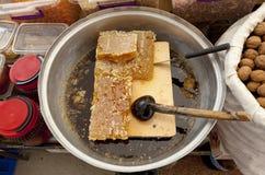 Cierre del peine de la miel para arriba Pedazos grandes de panal y de cuchara en el mercado del pueblo Foto de archivo