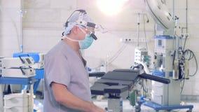 Cierre del retrato del cirujano para arriba Doctor con los aparatos médicos modernos que miran en cámara almacen de video