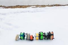 Cierre del sistema de carretes de la pesca para arriba en la nieve blanca Imagen de archivo libre de regalías