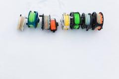 Cierre del sistema de carretes de la pesca para arriba en la nieve blanca Fotografía de archivo