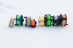 Cierre del sistema de carretes de la pesca para arriba en la nieve blanca Imagenes de archivo