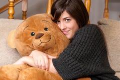 Cierre del sofá del oso de peluche del abrazo de la mujer que se sienta joven Fotos de archivo libres de regalías