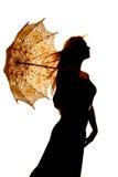 Cierre del soplo del pelo del paraguas de la mujer de la silueta Foto de archivo libre de regalías