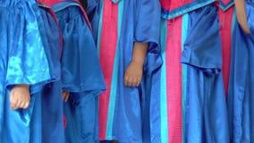 Cierre del vestido de la graduación del niño que lleva preescolar para arriba metrajes
