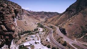 Cierre del vuelo del abejón cerca del acantilado grande para revelar el camino hermoso de la carretera y las pistas ferroviarias  almacen de video