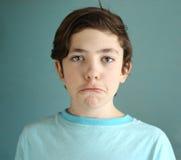 Cierre divertido que hace muecas del muchacho adolescente encima del retrato Fotos de archivo libres de regalías
