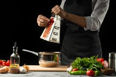 Cierre el chef& x27; manos de s, preparando una salsa de tomate italiana para los macarrones Pizza El concepto de la receta de co imagen de archivo libre de regalías