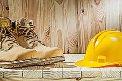 Cierre encima de botas y del casco de la visión en el fondo de madera imagen de archivo
