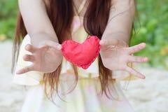 Cierre - encima de corazones de papel rojos en las manos de las mujeres Símbolo del amor Imágenes de archivo libres de regalías