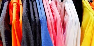 Cierre encima de la camisa de manga larga colorida en la suspensión en la tienda de la moda de los hombres fotografía de archivo