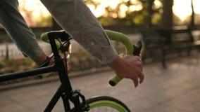 Cierre encima de la cantidad del timón - varón que completa un ciclo una bicicleta en el parque o el bulevar de la mañana Vista l almacen de video