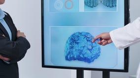 Cierre encima de la cantidad de la mano del científico que señala a una simulación del cerebro 3D metrajes