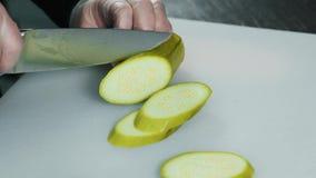CIERRE ENCIMA DE LA COMIDA: el cocinero tajó el calabacín verde en una tabla blanca con el cuchillo metrajes