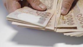 Cierre encima de la cuenta de las manos del dinero del baht tailand?s de los thousansds Cierre encima del billete de banco tailan metrajes