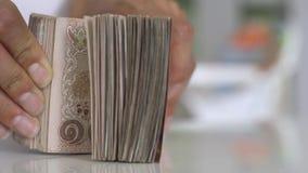 Cierre encima de la cuenta de las manos del dinero del baht tailand?s de los thousansds Cierre encima del billete de banco tailan almacen de metraje de vídeo