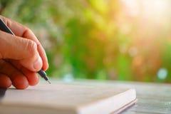 Cierre encima de la escritura humana de la mano algo Fotografía de archivo libre de regalías