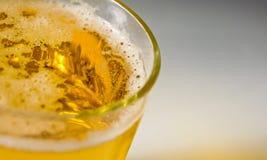 Cierre encima de la espuma de la espuma de la burbuja de la cerveza en vidrio o la taza para el fondo en la visión superior imagen de archivo libre de regalías