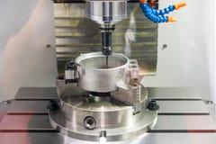 Cierre encima de la herramienta y del objeto que golpean ligeramente del tornillo en la fresadora del CNC de la alta exactitud en foto de archivo
