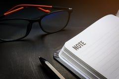 Cierre encima de la línea en blanco abierta cuaderno con la pluma negra y de los vidrios en fondo negro del escritorio en tono de fotos de archivo