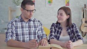 Cierre encima de la lectura joven y de estudiar de los pares un libro en un apartamento moderno metrajes