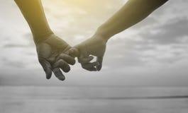Cierre encima de la mano del gancho mayor de los pares y x27; dedo meñique de s junto cerca de la playa en la playa, imagen blanc Imagen de archivo libre de regalías
