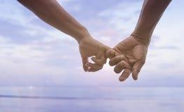 Cierre encima de la mano del gancho mayor de los pares y x27; dedo meñique de s junto cerca de la playa en la playa, imagen filtr Imagen de archivo