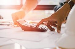 Cierre encima de la mano del hombre usando bonusOr calculador de la calculadora la otra remuneración a los empleados para aumenta fotografía de archivo