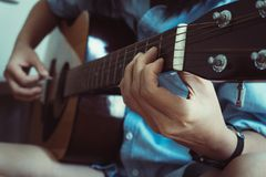 Cierre encima de la mano de la mujer asi?tica joven hermosa que toca la guitarra ac?stica mientras que se sienta en el sof? en ca foto de archivo