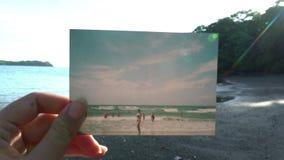 Cierre encima de la mano que sostiene la fotografía polaroid delante del concepto tropical hermoso del viaje de la puesta del sol metrajes