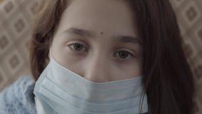 Cierre encima de la muchacha enferma triste de la cara con una máscara estéril en su cara que mira en el cierre de la cámara para almacen de video