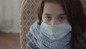 Cierre encima de la muchacha enferma triste del retrato que se sienta en la butaca con una máscara estéril en su cara dentro Conc almacen de video