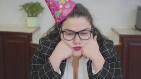 Cierre encima de la mujer regordeta triste del retrato en un casquillo del cumpleaños y vidrios elegantes que se sientan en la ta almacen de video