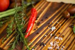 Cierre encima de la pimienta de chile, de las hierbas, de la sal y del grano de pimienta candentes en la tabla de madera Fondo ve fotos de archivo libres de regalías