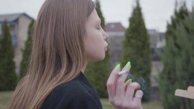 Cierre encima de la pintura joven bonita de la muchacha que fuma en lona mientras que se sienta en el patio trasero al aire libre almacen de video