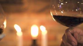 Cierre encima de las copas de vino que tintinean en fondo ardiente de las velas Copas que tintinean del hombre y de la mujer en l almacen de video