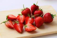 Cierre encima de las fresas frescas cortadas por la mitad y de las fresas enteras en tabla de cortar fotos de archivo libres de regalías