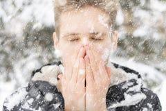 Cierre encima de las manos del calentamiento y de la calefacción del retrato del hombre cerca de la boca al aire libre en un día  fotografía de archivo