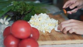 Cierre encima de las manos del cocinero con el cuchillo que corta el huevo hervido en el tablero de madera Concepto del alimento almacen de metraje de vídeo