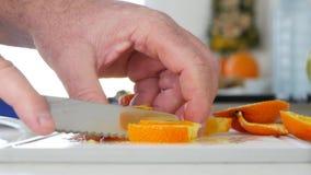 Cierre encima de las manos del hombre en la cocina que prepara una ensalada de fruta de naranjas almacen de metraje de vídeo