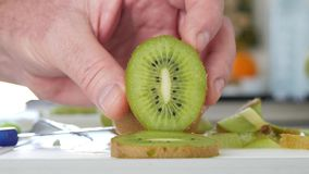 Cierre encima de las manos del hombre en la cocina que presenta una rebanada de Kiwi Fruit fresco y dulce metrajes
