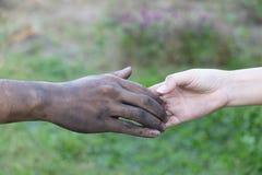 Cierre encima de las manos del hombre y de la mujer que tocan el lazo en el fondo borroso para el concepto del día de San Valentí foto de archivo libre de regalías