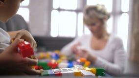 Cierre encima de las manos del muchacho que crean el juguete del constructor almacen de metraje de vídeo