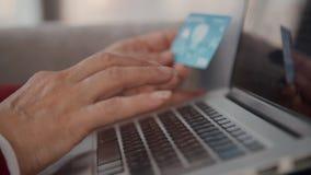 Cierre encima de las manos femeninas jubiladas que mecanografían el número de tarjeta de crédito en el teclado de ordenador portá metrajes