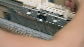 Cierre encima de las manos femeninas que trabajan en la máquina para hacer punto moderna Tela que teje de fabricación en la máqui almacen de video