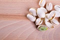Cierre encima de las nueces de pistacho con la cáscara en fondo de madera del piso foto de archivo libre de regalías